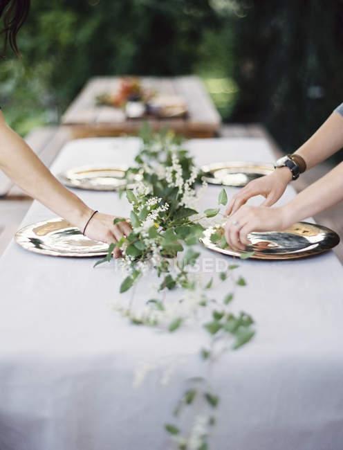 Colocación de cubiertos y platos sobre una mesa - foto de stock