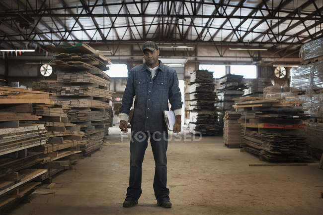 Man in work overalls with a clipboard. — Stock Photo