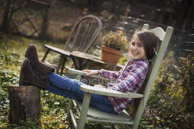 Дівчина сидить на дерев'яні стільці в саду — стокове фото