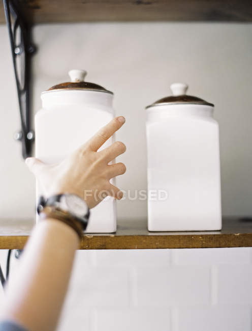Person reaching up to two storage jars — Stock Photo