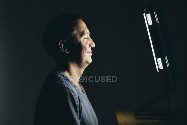 Mann sitzt vor einer Lichttherapie-box — Stockfoto