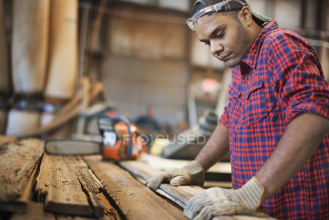 Mann misst und kontrolliert Bretter aus Holz — Stockfoto
