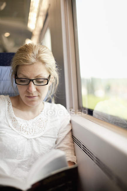 Woman sitting by a train window — Stock Photo