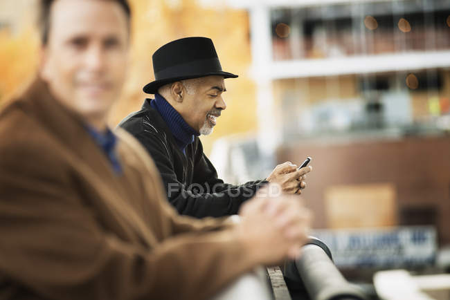 Men in coats leaning on a railing. — Stock Photo