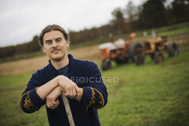 Homme appuyé sur une jardin houe — Photo de stock