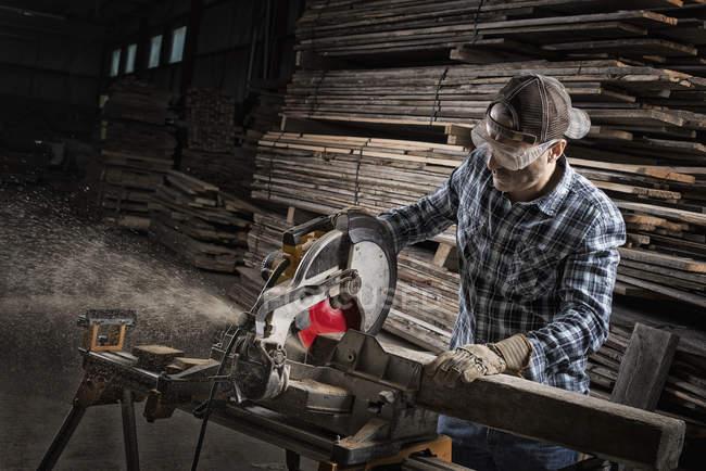 Homme à l'aide d'une scie circulaire pour couper du bois — Photo de stock