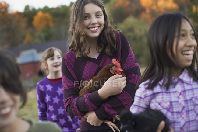 Groupe de quatre enfants élevant des poulets — Photo de stock