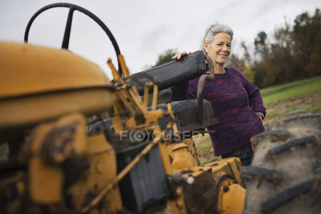 Farmer woman by a tractor. — Stock Photo
