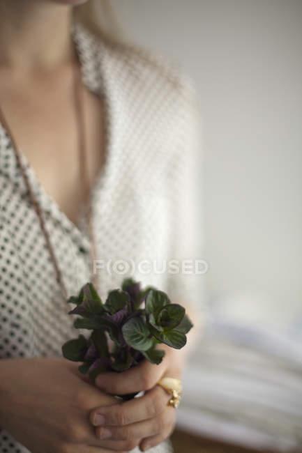 Frau mit grünen Pflanzenblättern — Stockfoto