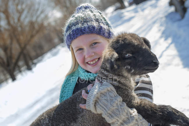 Girl holding a young lamb. — Stock Photo