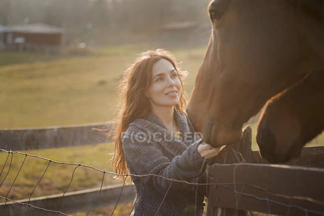 Frau streichelt zwei Pferden die Schnauze — Stockfoto