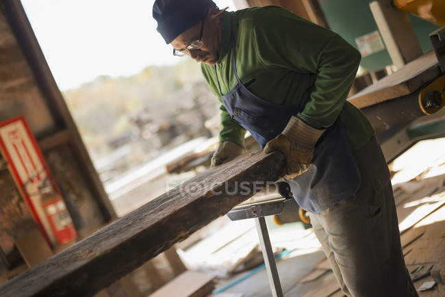 Man examining a large plank of cut wood — Stock Photo