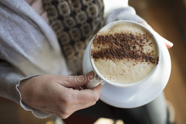 Woman holding a full cup of cappuccino — Stock Photo