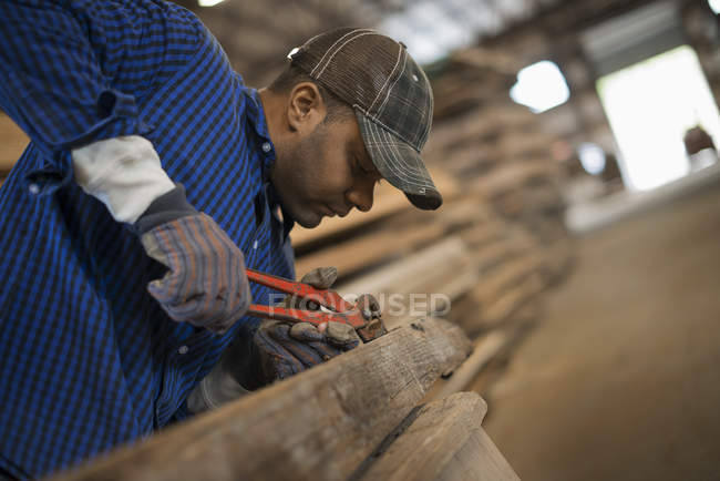Man working in a reclaimed timber yard. — Stock Photo