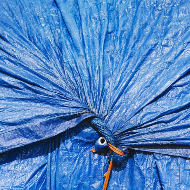 Lona azul, se reuniram e amarrado — Fotografia de Stock