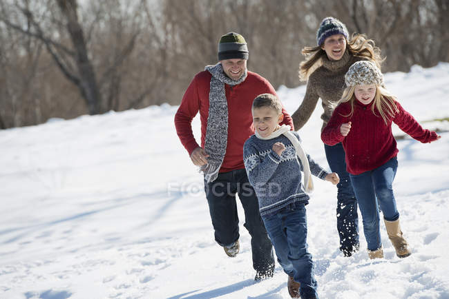 Two adults chasing two children. — Stock Photo