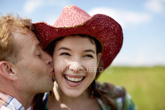 Woman  being kissed on the cheek by man. — Stock Photo