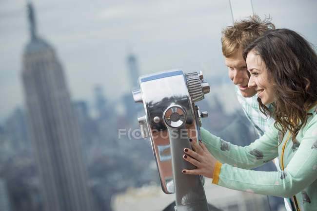 Couple looking through the telescope. — Stock Photo
