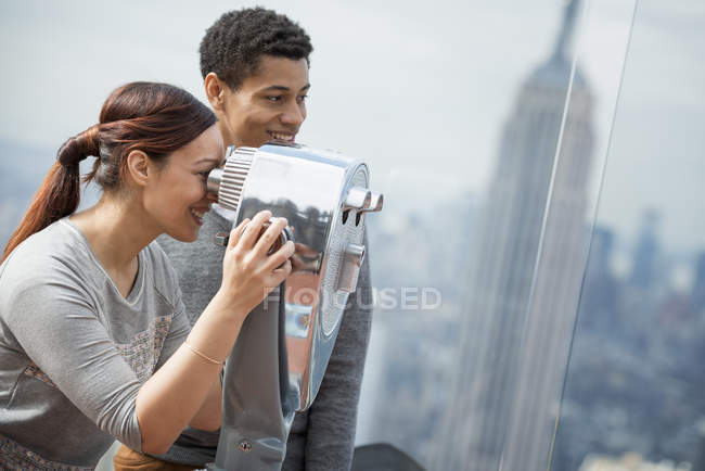Couple à la recherche à travers le télescope — Photo de stock