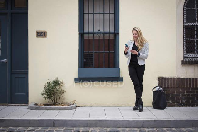 Mujer de pie en una acera de la calle - foto de stock