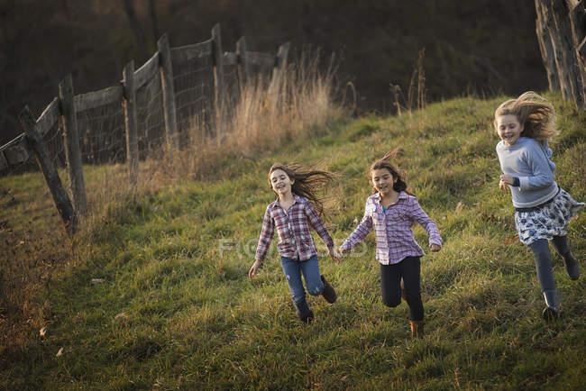 Trois enfants dévalant une colline — Photo de stock