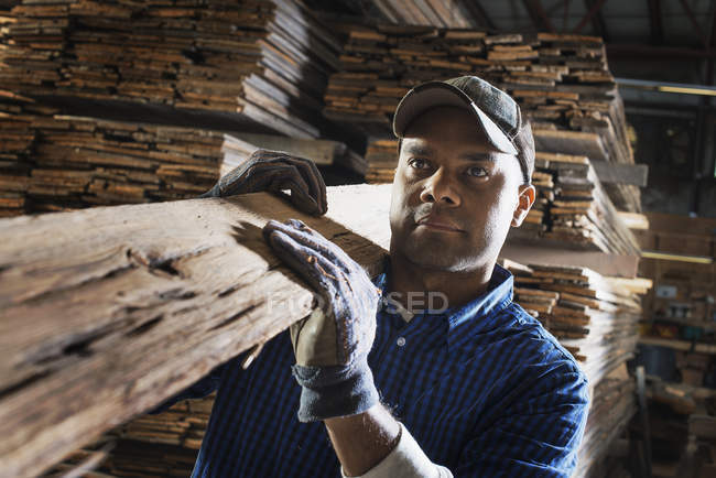 Man carrying a large plank — Stock Photo
