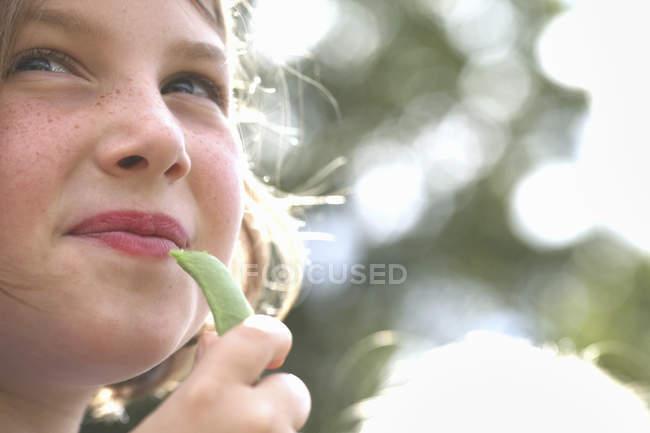 Chica comiendo un guisante recién cogido - foto de stock