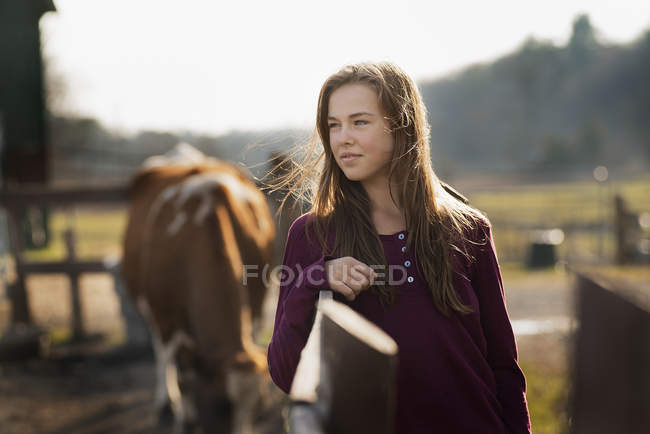 Girl leaning on a paddock fence — Stock Photo