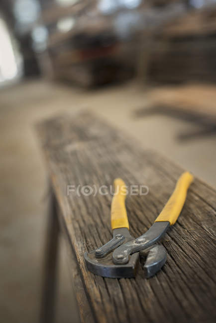 Pair of pliers on plank of wood — Stock Photo