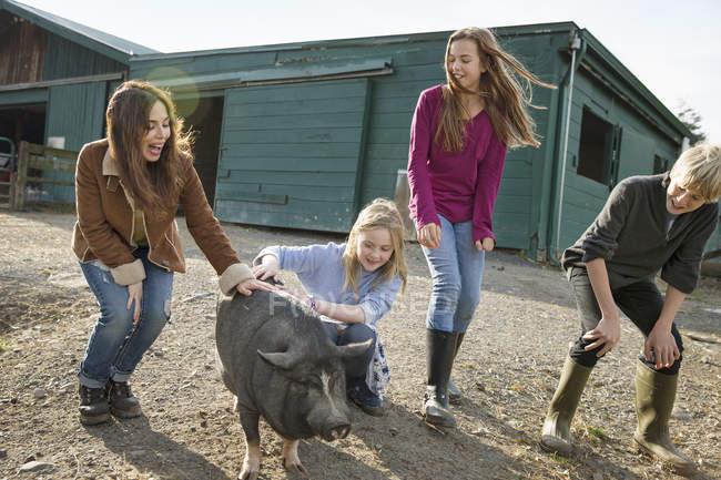 Kinder und eine junge Frau mit einem großen Schwein — Stockfoto