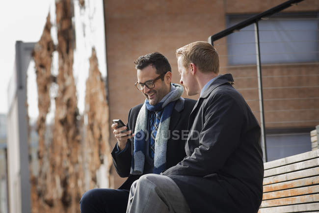 Men sitting on a bench with mobile phone. — Stock Photo
