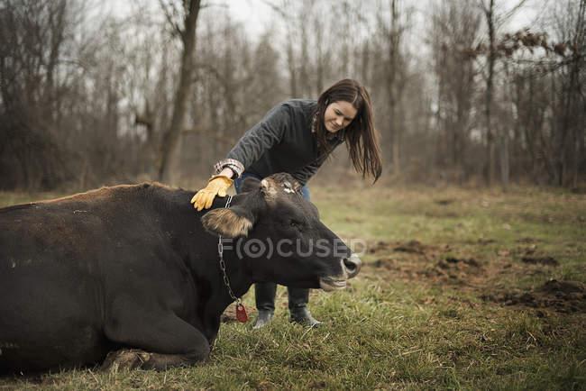 Frau arbeitet auf Hof und tendenziell Kuh — Stockfoto