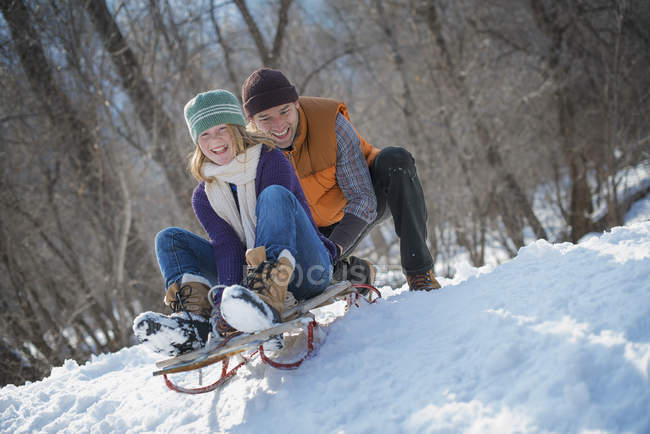 Man pushing woman from the top of a slope on a toboggan. — Stock Photo