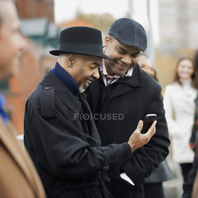 Men side by side with mobile phone — Stock Photo