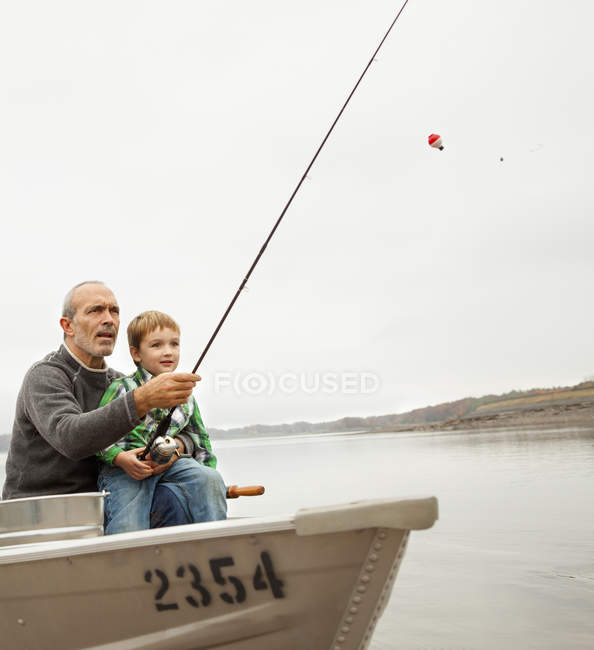 Man showing boy how to fish — Stock Photo
