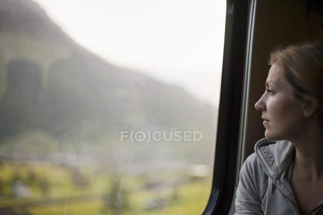 Woman sitting by a train window — Stock Photo