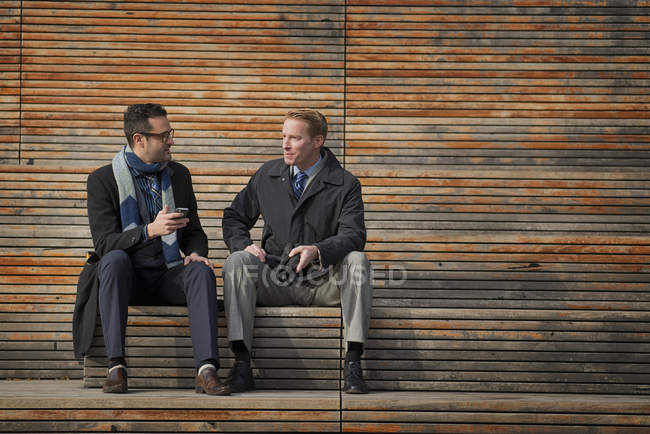 Men sitting on a bench outside — Stock Photo