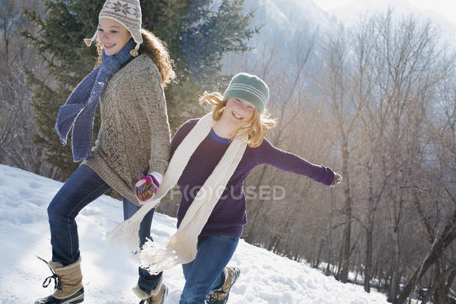 Woman and a child running across the snow. — Stock Photo