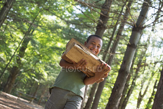 Boy carrying firewood through the woods. — Stock Photo