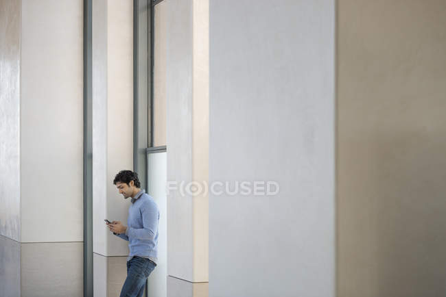 Man in a blue sweater using phone — Stock Photo