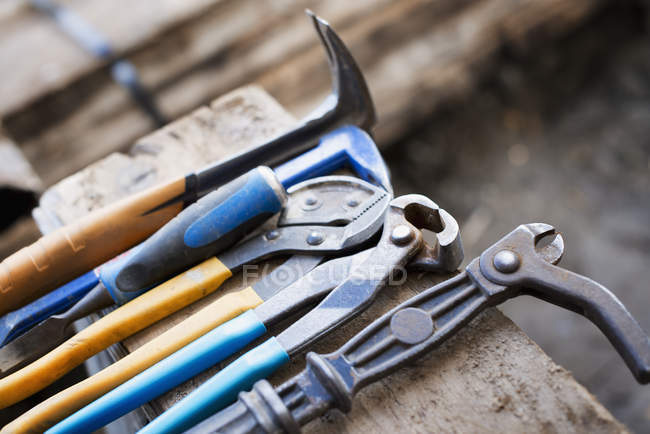 Range of pliers and chisels on a plank of wood. — Stock Photo