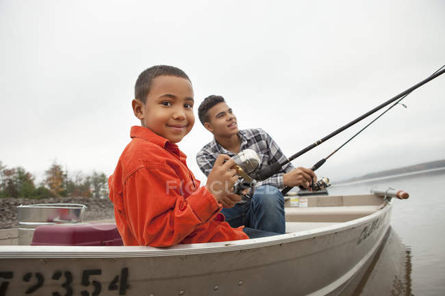 Two boys fishing from a boat. — Stock Photo