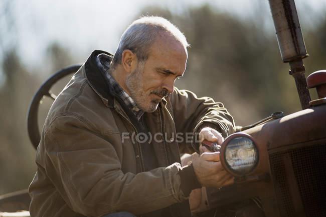 Hombre que trabajaba en una granja orgánica - foto de stock