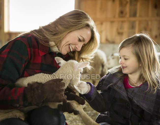 Frau und ein Kind, ein kleines Lamm streicheln — Stockfoto