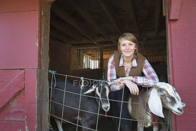 Girl leaning on the barrier of the goat shed — Stock Photo