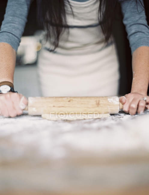 Woman Rolling out pastry on a table top — Stock Photo