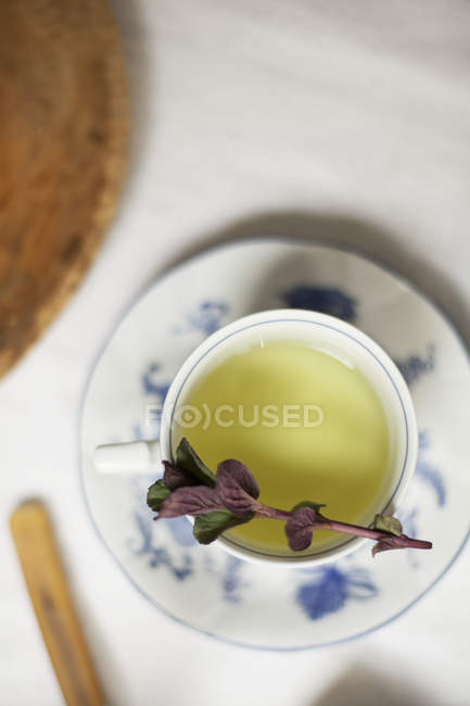 Clear coloured tea in a china cup — Stock Photo