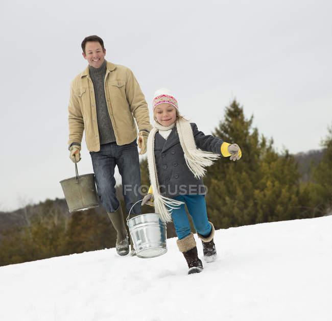 Hombre y niño llevando baldes - foto de stock