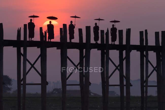 Siluetas de monjes en U Bein Bridge - foto de stock