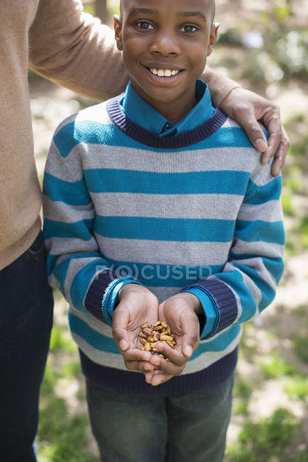 Boy holding a handful of nuts. — Stock Photo